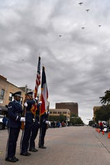 Members of the Commemorative Air Force fly the Missing Man formation while the Dyess Air Force Base Honor Guard stands at attention during Saturday's Veterans Day parade.