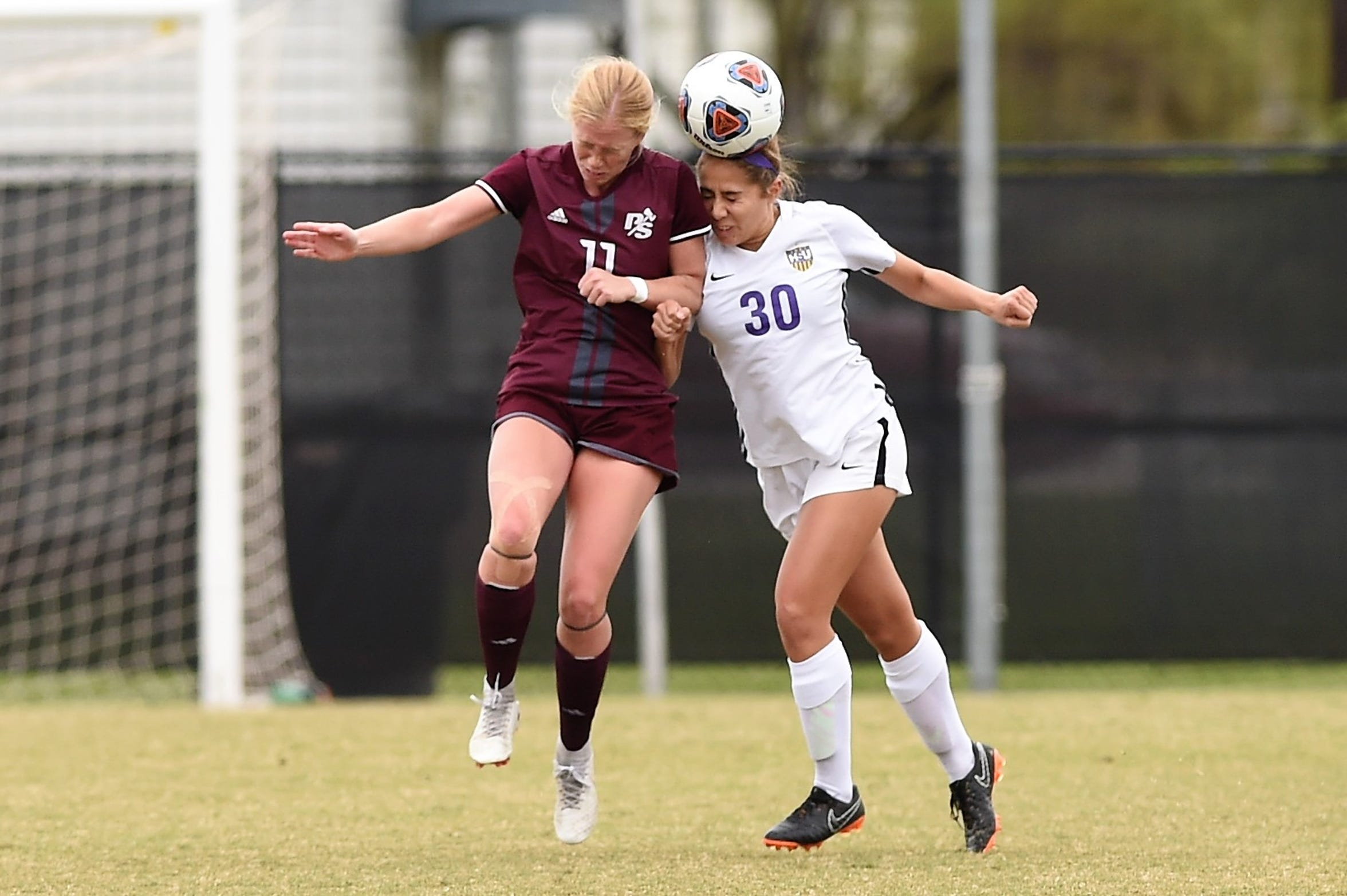 Hardin-Simmons freshman Mackensie Moreno (30) heads the ball away from Puget Sound's Gabbie Berg (11) during the NCAA tournament's first round. Moreno has developed into a quality defender for the Cowgirls this season.