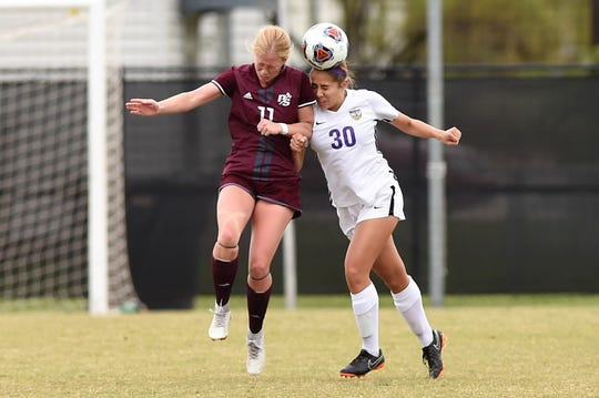 Hardin-Simmons' Mackensie Moreno (30) heads the ball away from Puget Sound's Gabbie Berg (11) during the NCAA tournament's first round Saturday.