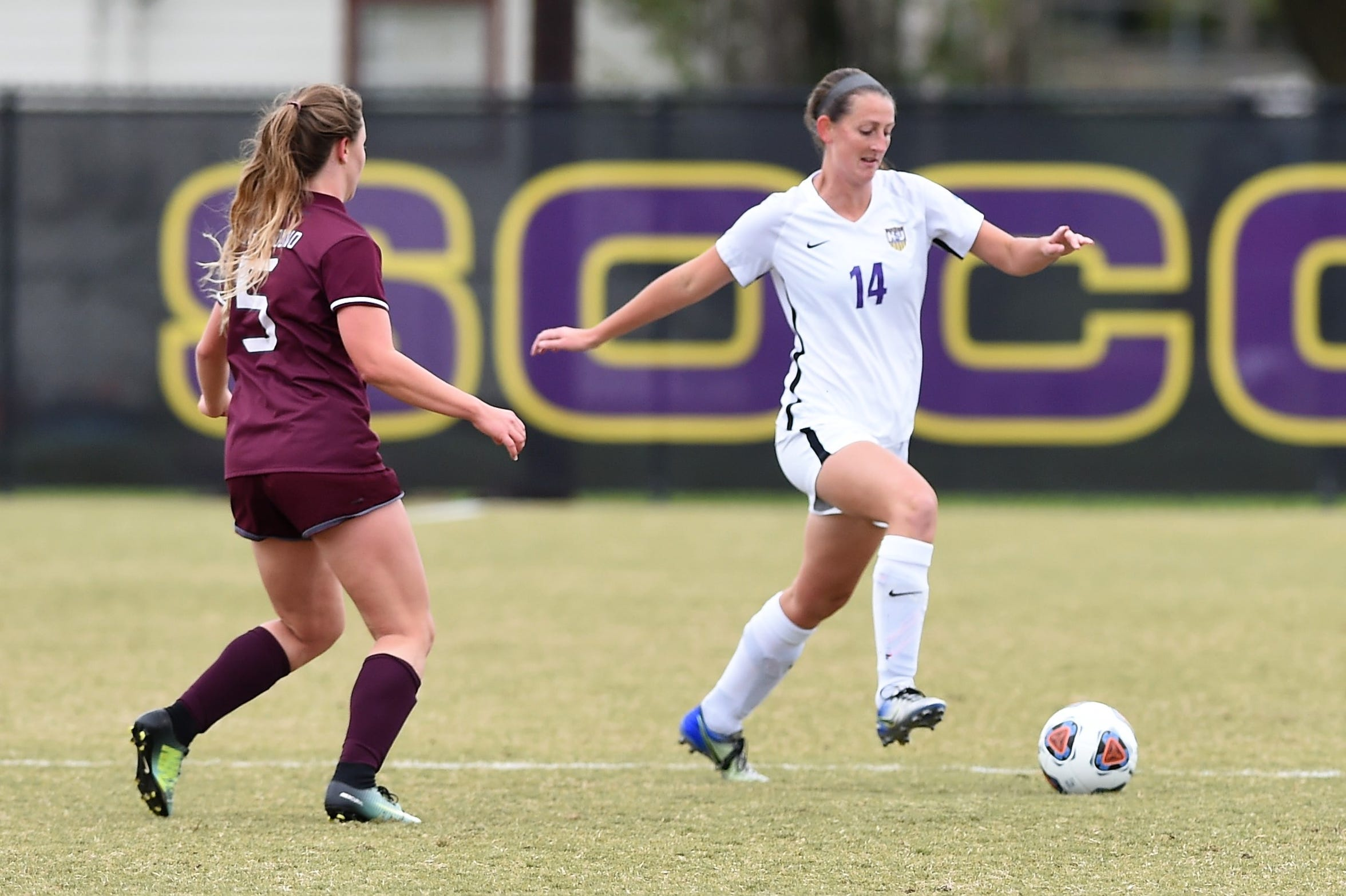 Hardin-Simmons defender Sarah Krisa (14) carries the ball past Puget Sound's Lura Morton (5) during the NCAA tournament's first round. Krisa's move to the back line was a key to stabilizing the Cowgirls' defense this season.