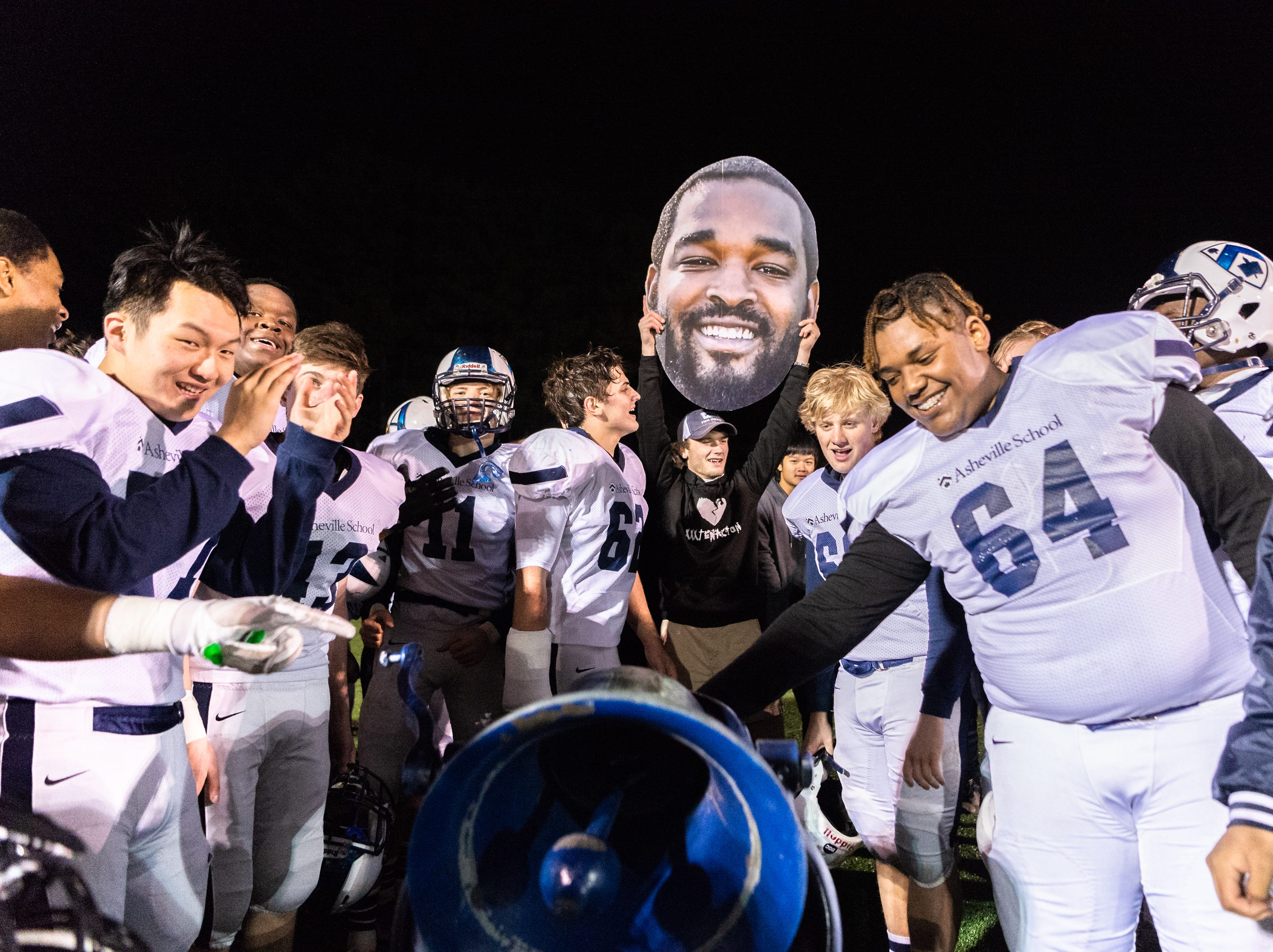 The Asheville School football team celebrates their 33-28 win over Southlake Christian by ringing a bell behind their endzone after their Friday night second round semifinal game Nov. 9, 2018. Asheville School's win advances them to the NCISAA Division III state championship game.