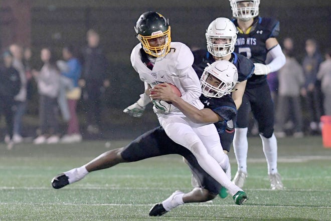 Christ School's Aydan White gets wrapped up by Charlotte Christian's Jeremiah Gray as he runs the ball during the NCISAA Division I State Championship game at Charlotte Christian School on Nov. 9, 2018. The Greenies fell to the Knights 43-14.