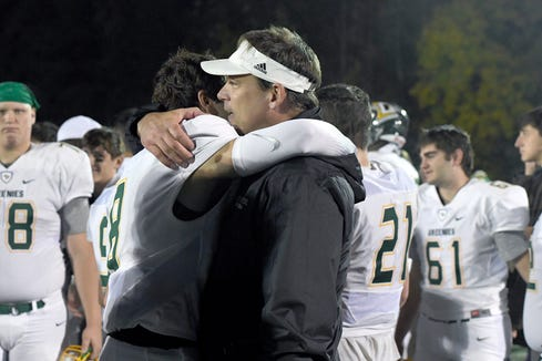 Christ School quarterback Navy Shuler gets a hug from his dad, Heath, after the Greenies lost 43-14 in the NCISAA Division I State Championship game at Charlotte Christian School on Nov. 9, 2018.