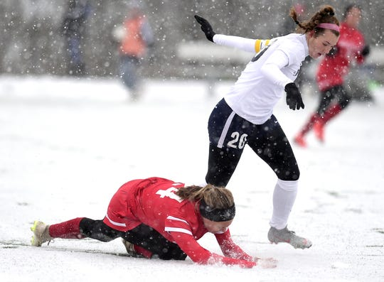 Wheatley's Julia Braito (24) falls on the snowy field after attempting to take control of the ball from Chenango Forks Emma Bough (20) during first half of Chenango Forks vs. Wheatley, NYSPHSAA Girls Soccer Championship, Cortland High School, Cortland, NY. Saturday, November 10, 2018.