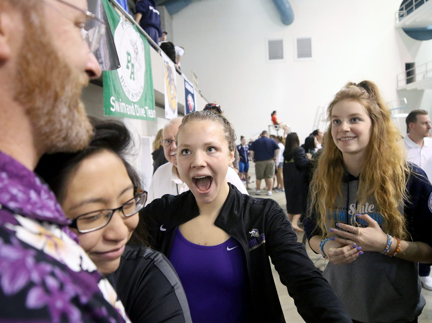 The North Kitsap Girls swim team won the team title at the 2018 2A Girls State Swim & Diving Championships on Saturday, November, 10, 2018 at the King County Aquatics Center, in Federal Way.  North Kitsap swimmers pose with the swimming title trophy. Swimmer Eleanor Beers reacts after coach Greg Braun won the coach of the meet.