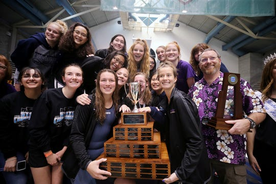 North Kitsap girls swim coach Greg Braun poses with his swimmers and a first-place trophy following the Class 2A state swim and diving championships at the King County Aquatic Center in Federal Way in November.