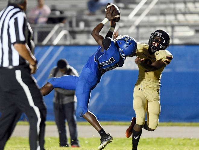 Reggie Reynolds of Heritage catches a pass over Eau Gallie defender Dink Jackson (9) during Friday's first round playoff game.
