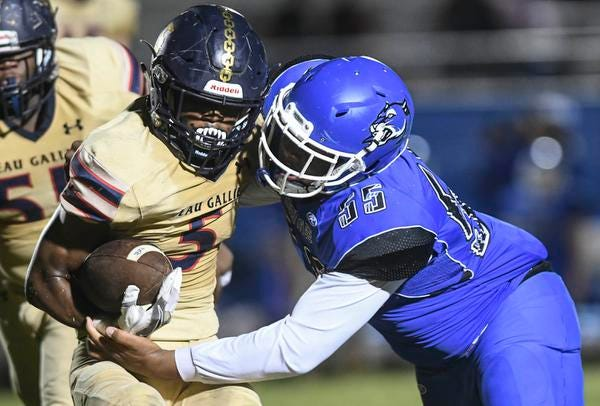 Jarrad Baker Jr. of Eau Gallie is stopped by Damanee Thomas of Heritage During Friday's first round playoff game.