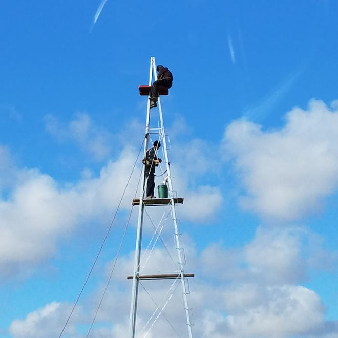 Amish work diligently on a new windmill at the Crawford County Fairgrounds.