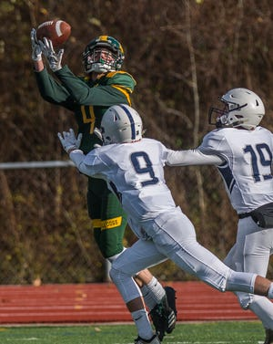 Burr and Burton's #4 Jake Nicholson makes the catch over coverage from Fair Haven's #9 Aubrey Ramey and #19 Brett Huntley during the Vermont Div. 2 high school football championship in Rutland on Saturday, Nov. 10, 2018. Burr and Burton won, 63-14.