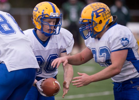 Poultney's Caden Capman, left, hands off to Jacob Allen during the Division III high school football championship game at Rutland High School on Saturday, Nov. 10.