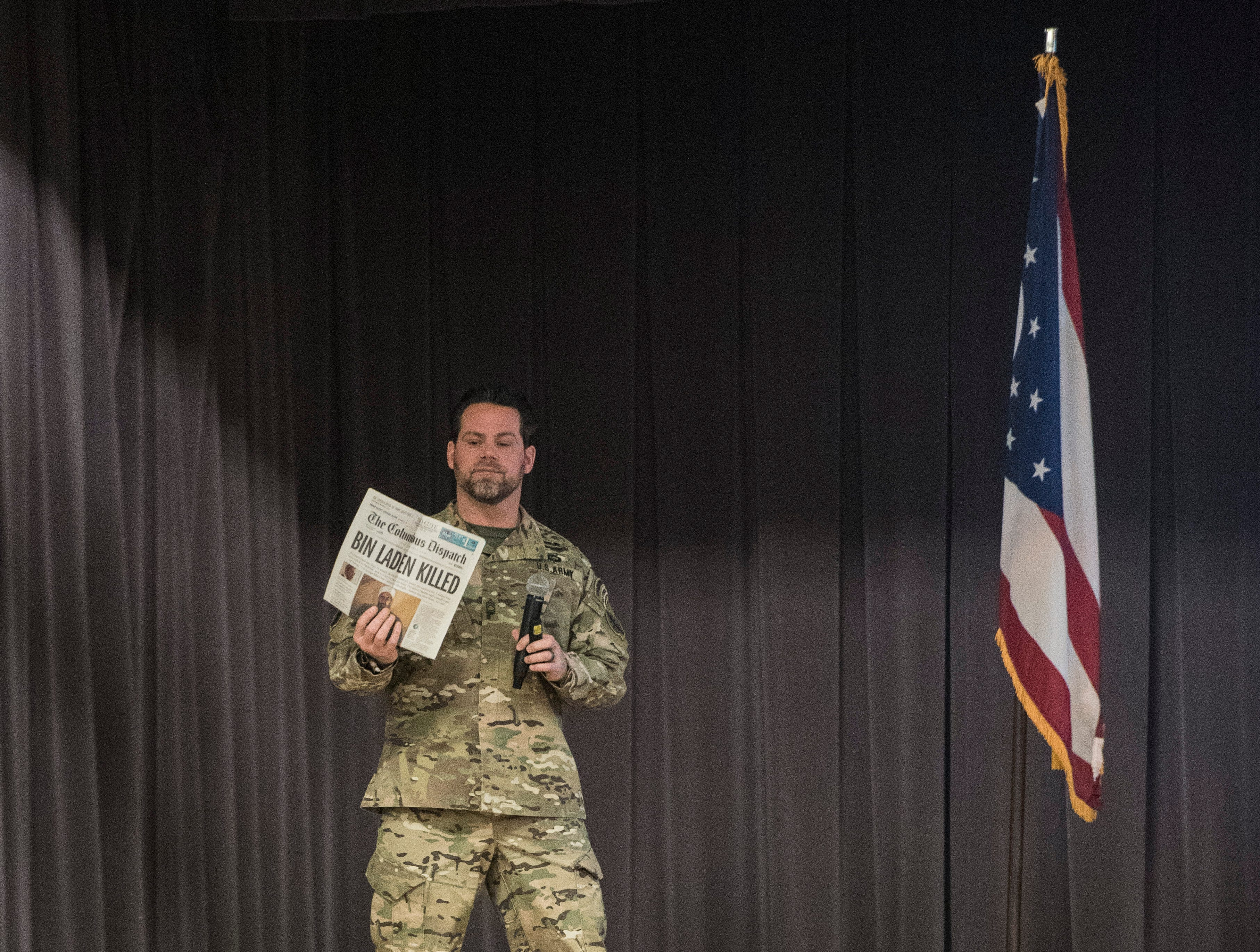 Former Zane Trace graduate Sean Clifton holds up a newspaper headlining the death of Osama bin Laden and what it meant to him and others in the military.