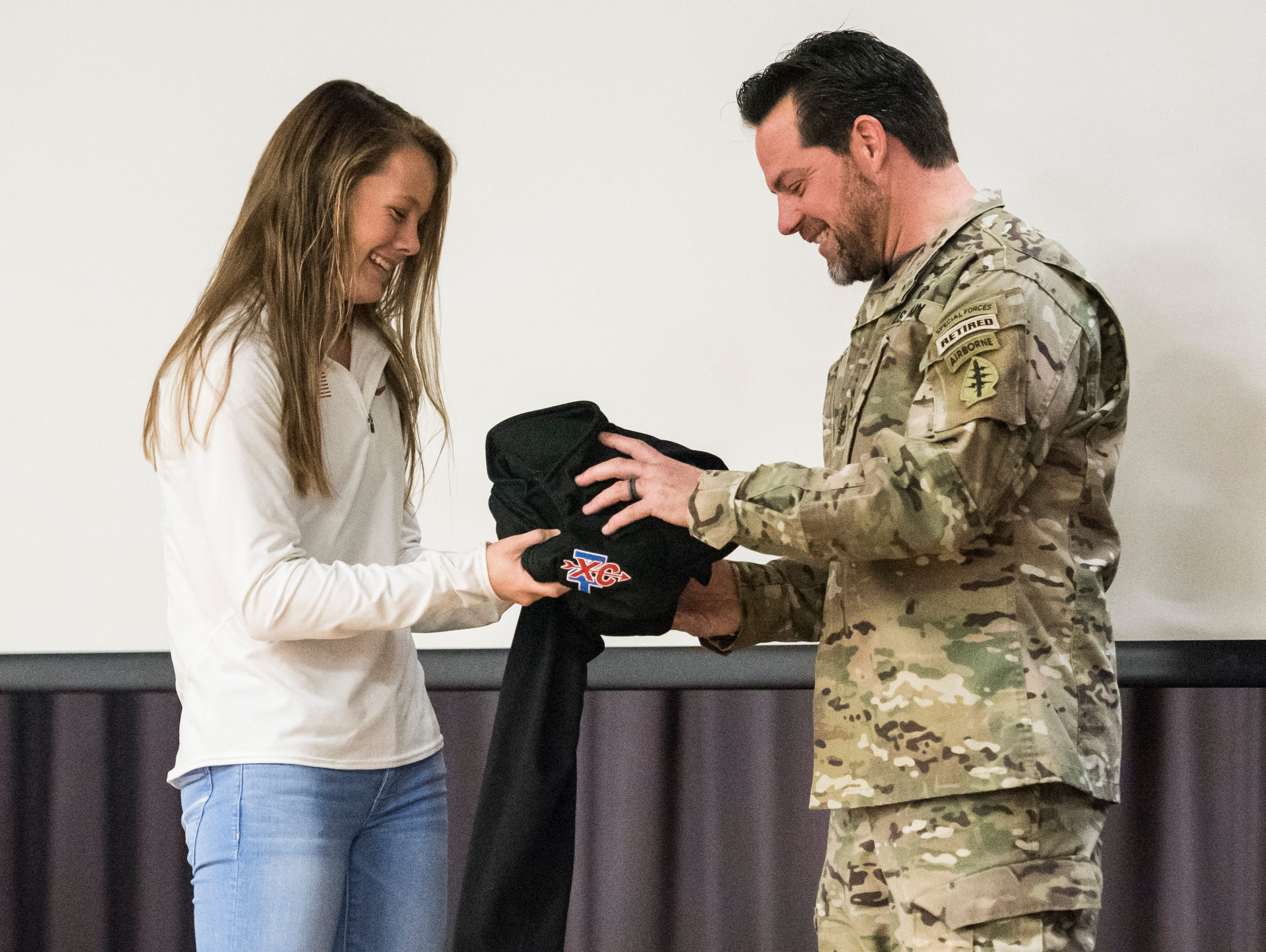 Senior Abbey Mohan gives Sean Clifton, a former Zane Trace cross-country runner, some running gear as a thank you for talking to the school about his experiences as an American soldier.