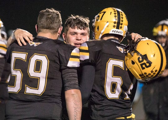 Paint Valley junior Brock Hill, middle, hugs seniors Hunter Gibson and Quintin Daniel after their 40-6 loss Friday night during a regional semi-final game against Shadyside.