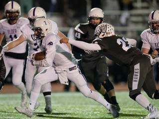 Elder quarterback Matthew Luebbe  (7) runs past Lakota East fullback Michael Howard (22) during the second round Division I playoff football game between Elder and Lakota East on Friday, Nov. 9, 2018 in Mason.
