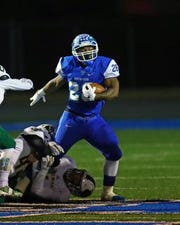 Winton Woods' RB Miyan Williams attempts to escape the grasp of Little Miami defender Sean Buscher as he runs the ball for the Warriors.