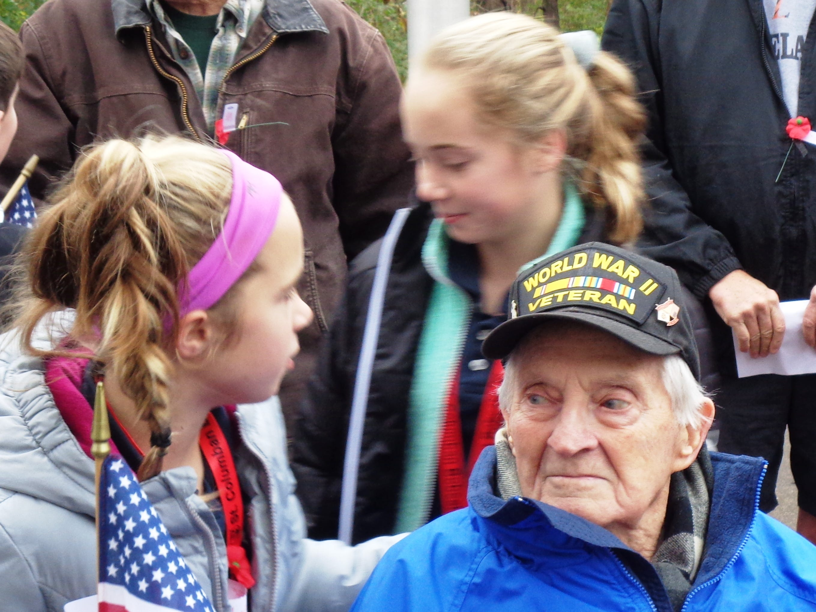 St. Columban students Reagan and Riley Ferris shared a hug with their grandfather World War II Navy veteran Ken Ferris at the ceremony honoring veterans in Loveland, Ohio Friday, Nov. 9, 2018.