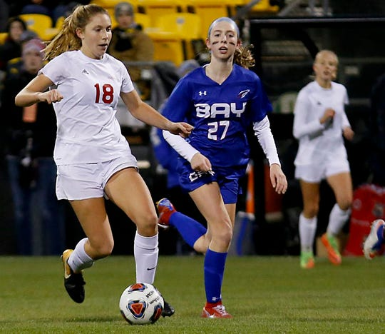 Indian Hill midfielder Ellie Podojil is pursued by Bay Village Bay midfielder Alexis Knapp during their Division II Championship soccer game at MAPFRE Stadium in Columbus Friday, Nov. 9, 2018.