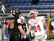 Zeke Correll (75) of Anderson and Spencer Klopfenstein of Troy shake at midfield before the start of the OHSAA Division II Region Semifinal, November 9, 2018.