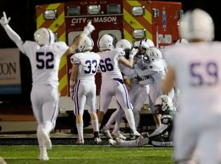 Elder linebacker Zach Bischoff  (9) is surrounded by teammates after scoring a touchdown on an interception return during the second round Division I playoff football game between Elder and Lakota East on Friday, Nov. 9, 2018 in Mason.