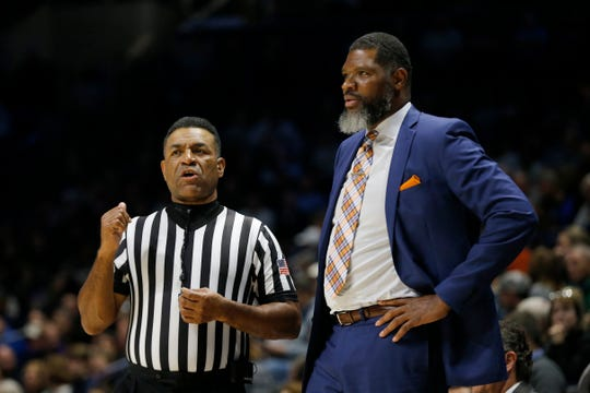 Evansville Aces head coach Walter McCarty talks with an official on the sideline in the first half of the NCAA basketball game between the Xavier Musketeers and the Evansville Aces at the Cintas Center in Cincinnati on Saturday, Nov. 10, 2018. Xavier led 49-45 at halftime.