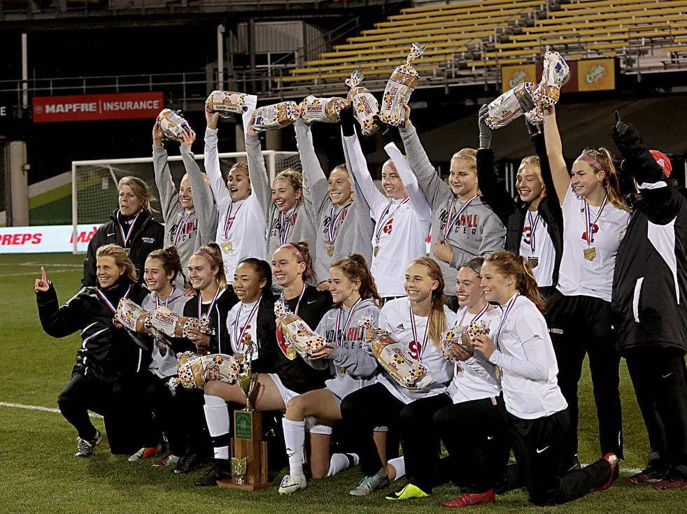 The Indian Hill girls soccer team holds up their symbolic loaves of bread as they pose for a team photo after defeating Bay Village Bay in their Division II Championship soccer game at MAPFRE Stadium in Columbus Friday, Nov. 9, 2018.