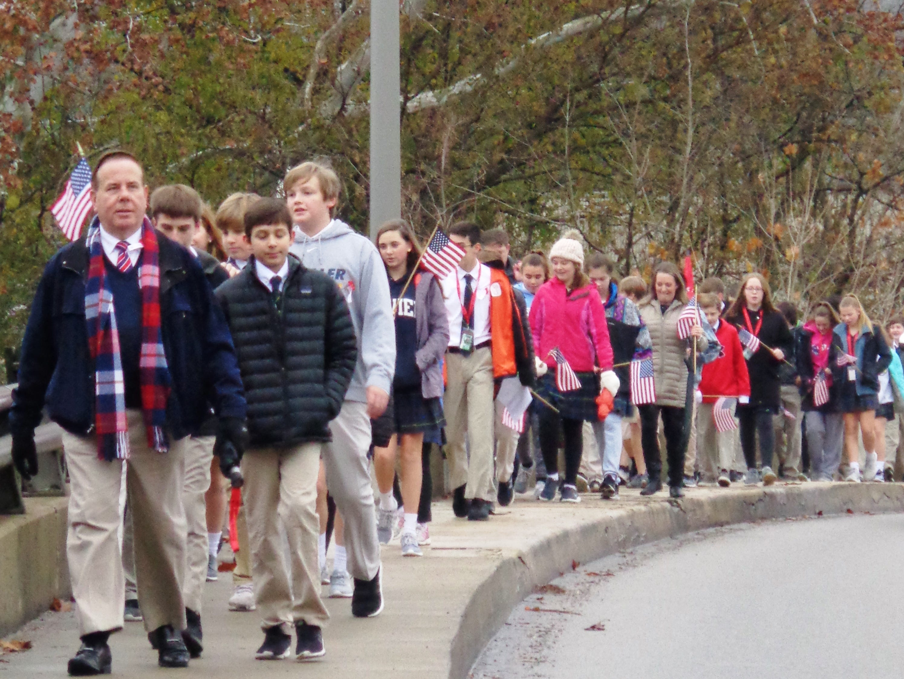 St. Columban School students led by teacher Chad Drinnen parade across the bridge in Loveland on the way to their annual Veterans Day ceremony at Loveland Veteran's Memorial Park.