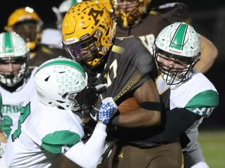 Kettering Alter running back  C.J. Hicks Jr is tackled by Hamilton Badin defenders during their playoff game, Friday, Nov. 9, 2018.