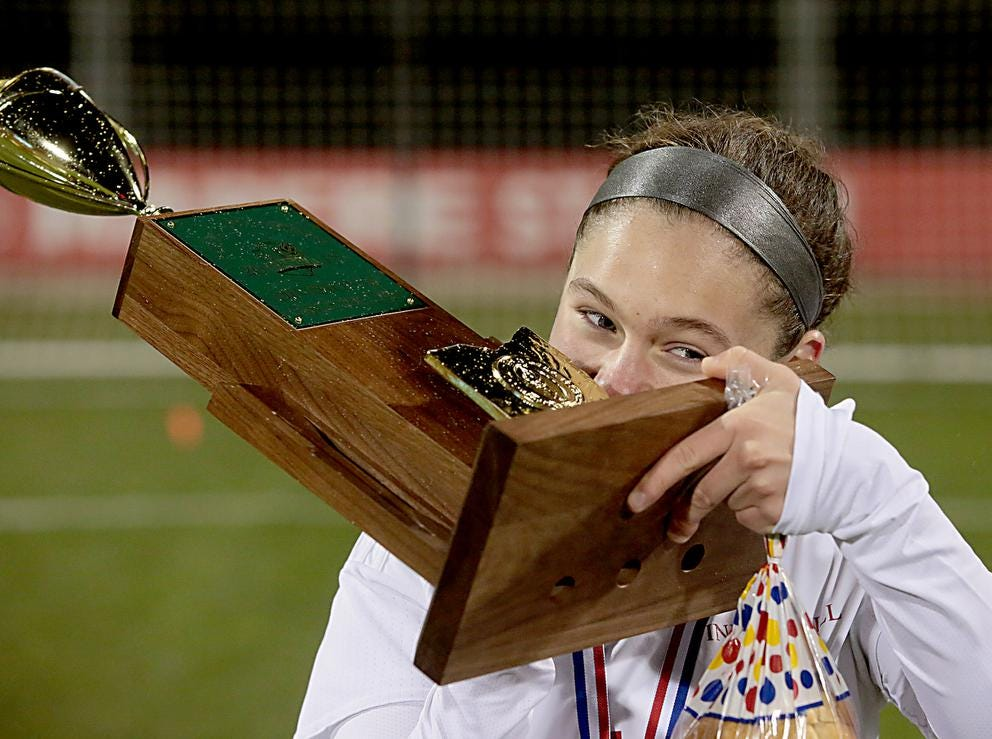 Faye Hardek, of Indian Hill, takes a bite of the championship trophy after defeating Bay Village Bay in their Division II Championship soccer game at MAPFRE Stadium in Columbus Friday, Nov. 9, 2018.