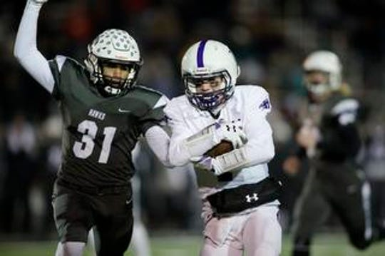 Elder quarterback Matthew Luebbe  (7) is tackled by Lakota East defensive back Dylan Sawyer (31) during the second round Division I playoff football game between Elder and Lakota East on Friday, Nov. 9, 2018 in Mason.