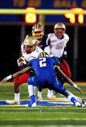 Edison's Josiah Smith-Velez is about to be tackled by North Brunswick's Myles Baileyduring the first half of a Central Group V semifinal on Friday, Nov. 9, 2018.