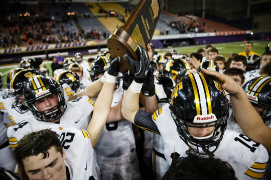 Southeast Polk holds up their state participant trophy after falling to Cedar Falls 12-26 during their 4A state football semi-final game on Friday, Nov. 9, 2018, in Cedar Falls.
