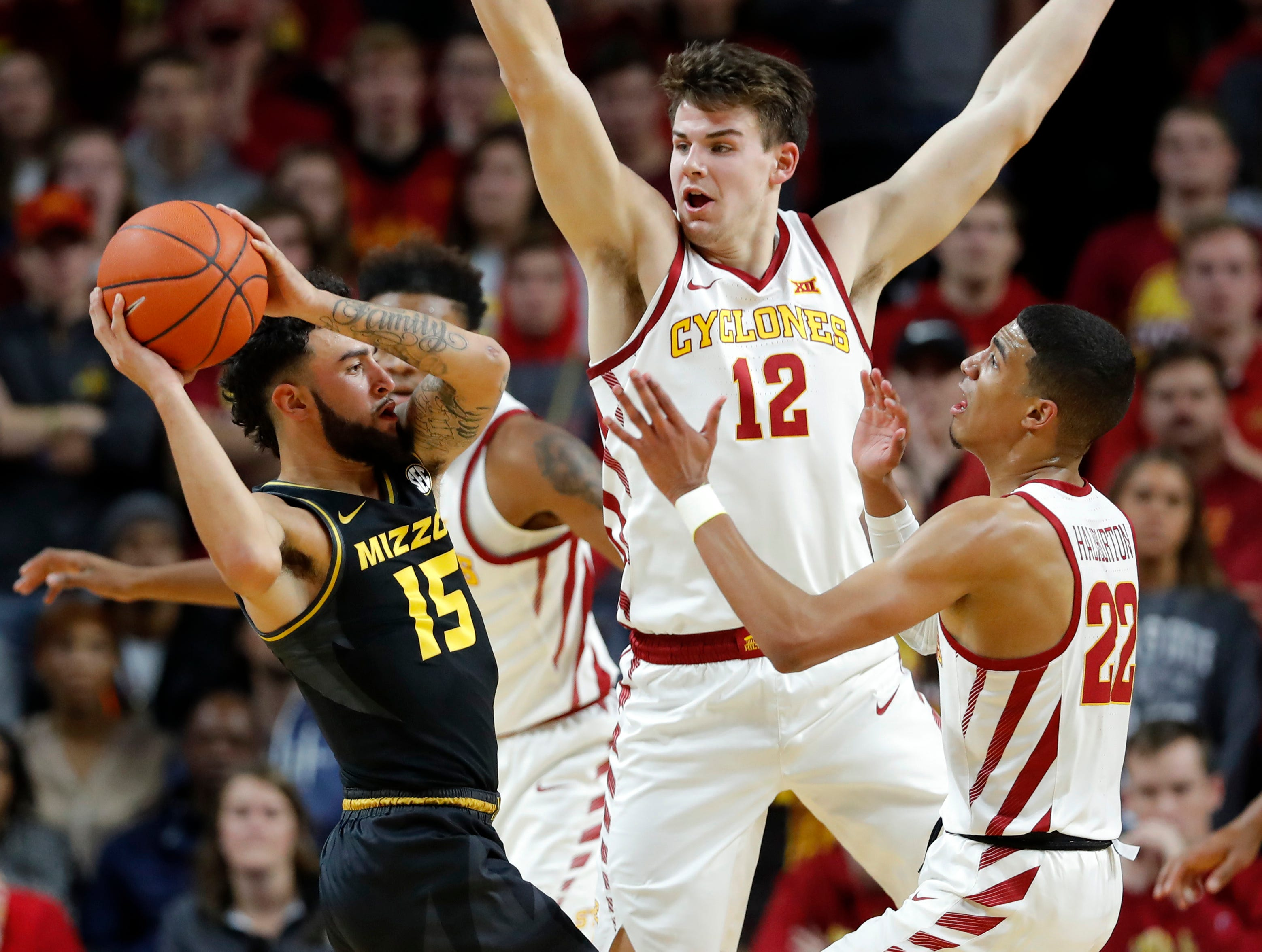 Missouri guard Jordan Geist (15) tries to pass around Iowa State forward Michael Jacobson (12) and guard Tyrese Haliburton, right, during the first half of an NCAA college basketball game, Friday, Nov. 9, 2018, in Ames, Iowa.