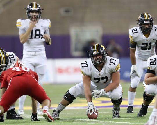 Southeast Polk's Aaron Martinez (77) prepares to make the snap to quarterback Josiah Cole (18) in a Nov. 9 state semifinal against Cedar Falls at the UNI Dome.