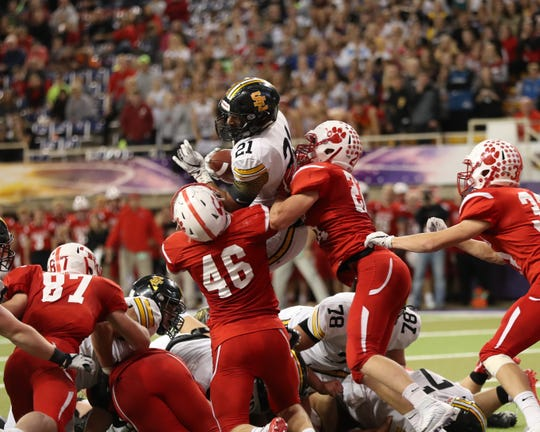 Nov 9, 2018; Cedar Falls, IA, USA; Southeast Polk Rams Gavin Williams (21) is stopped by Cedar Falls Tigers Jack Campbell (46) at the UNI Dome. The Rams lost to the Tigers 26-12.