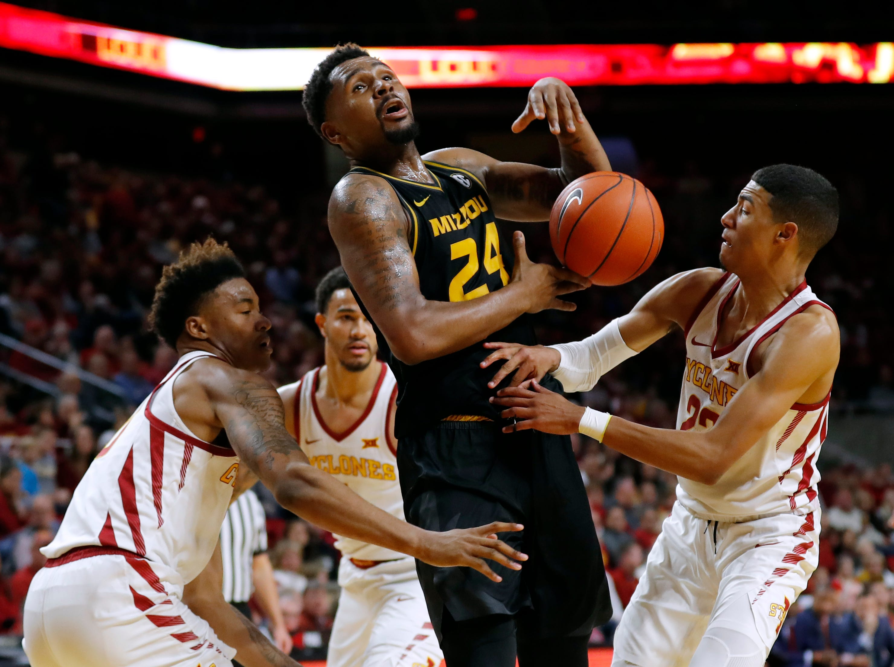 Missouri forward Kevin Puryear, center, is fouled while driving to the basket between Iowa State's Zion Griffin, left, and Tyrese Haliburton, right, during the second half of an NCAA college basketball game, Friday, Nov. 9, 2018, in Ames, Iowa.