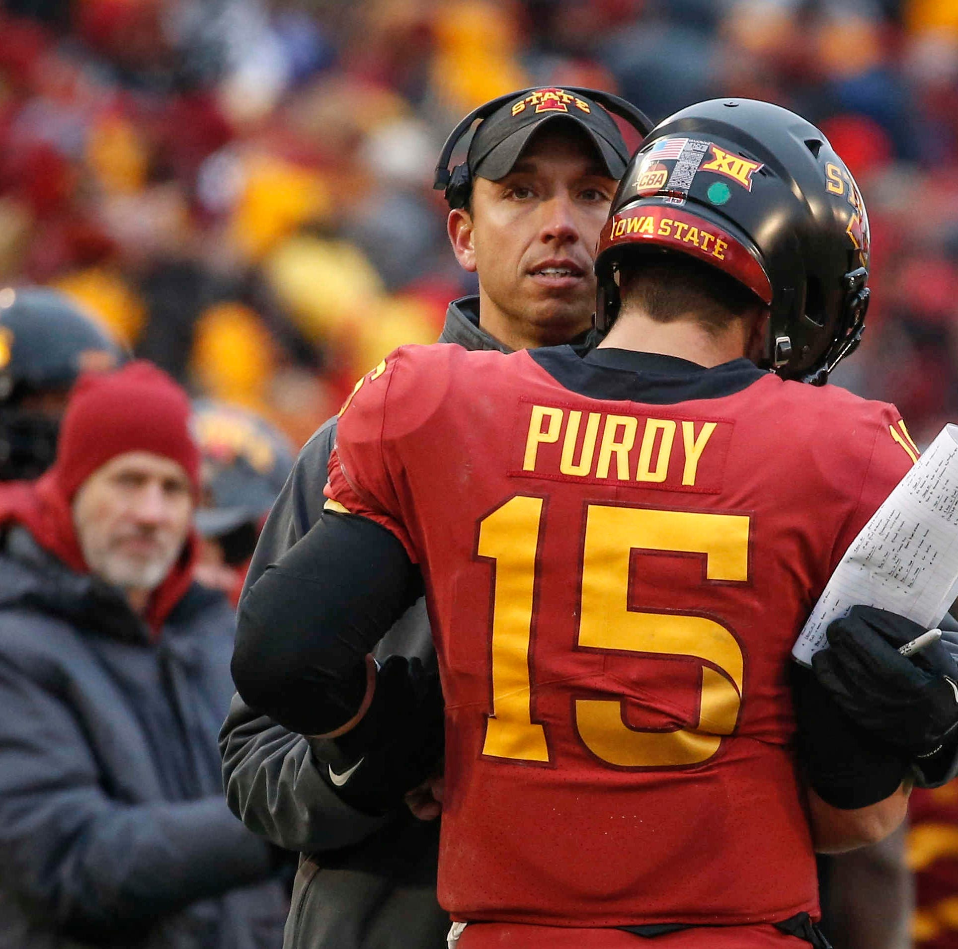 Iowa State quarterback Brock Purdy is hugged by...