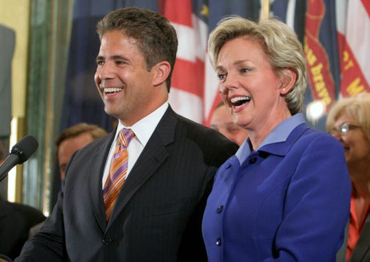 Michigan Gov. Jennifer Granholm, right, and Senate Majority Leader Mike Bishop, R-Rochester, smile during a news conference in June 2007 at the state Capitol in Lansing announcing a deal on a replacement for Michigan's main business tax.  The agreement would replace all of the roughly $1.9 billion a year now brought in by the Single Business Tax, which expires at the end of this year.