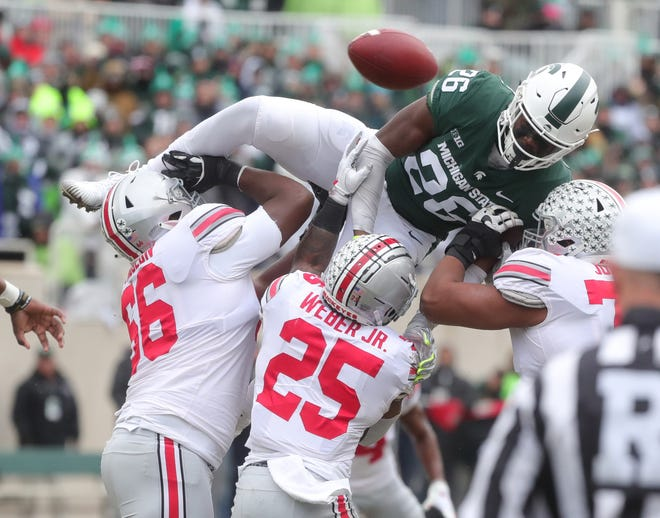 Michigan State's Brandon Bouyer-Randle goes over Ohio State blockers defending a pass during first half action Saturday, Nov. 10, 2018, at Spartan Stadium, in East Lansing.