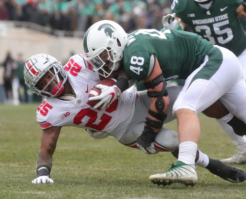 Michigan State's Kenny Willekes tackles Ohio State's Mike Weber Jr. during first half action Saturday, November 10,2018 at Spartan Stadium, in East Lansing, Mich.