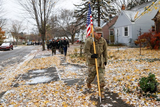 Army recruiter Robert Robinson carries the American flag and walks with his rucksacks toward Ferndale during the 22 Ruck March in Royal Oak, Saturday, Nov. 10, 2018.  The event hopes to bring awareness to veteran suicide. On average, 22 veterans commit suicide per day in the United States.