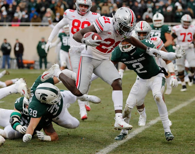 Ohio State receiver Parris Campbell leaps over Michigan State linebacker Byron Bullough (38) to score on a 1-yard run during the first half Saturday, Nov. 10, 2018, in East Lansing.