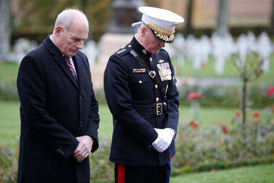White House Chief of Staff John Kelly, left, and Chairman of the Joint Chiefs of Staff, Marine Gen. Joseph Dunford bow during for a ceremony at the Aisne Marne American Cemetery near the Belleau Wood battleground, in Belleau, France, Saturday, Nov. 10, 2018.