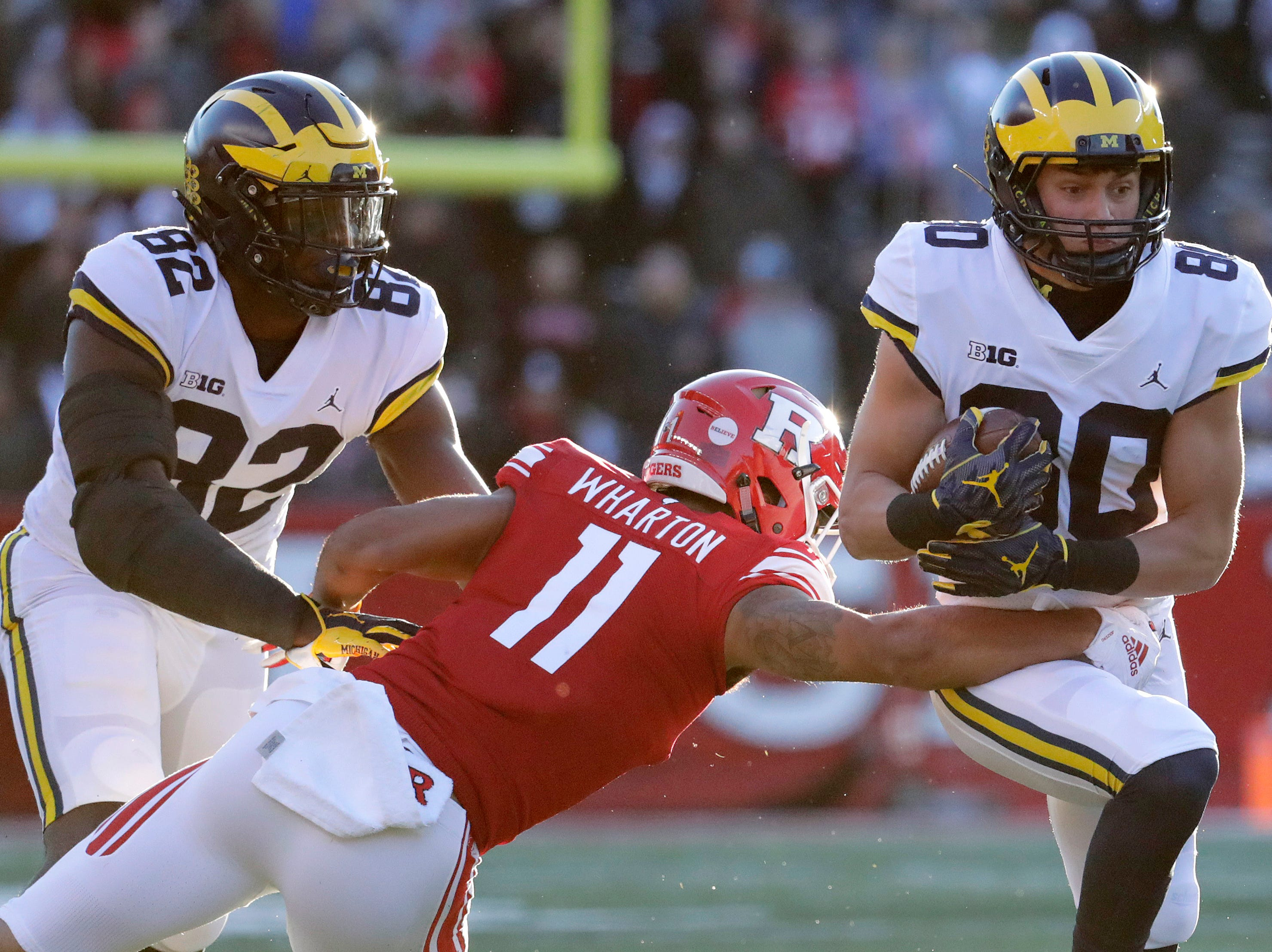 Michigan wide receiver Oliver Martin runs with the ball as Rutgers defensive back Isaiah Wharton tries to wrap him up.