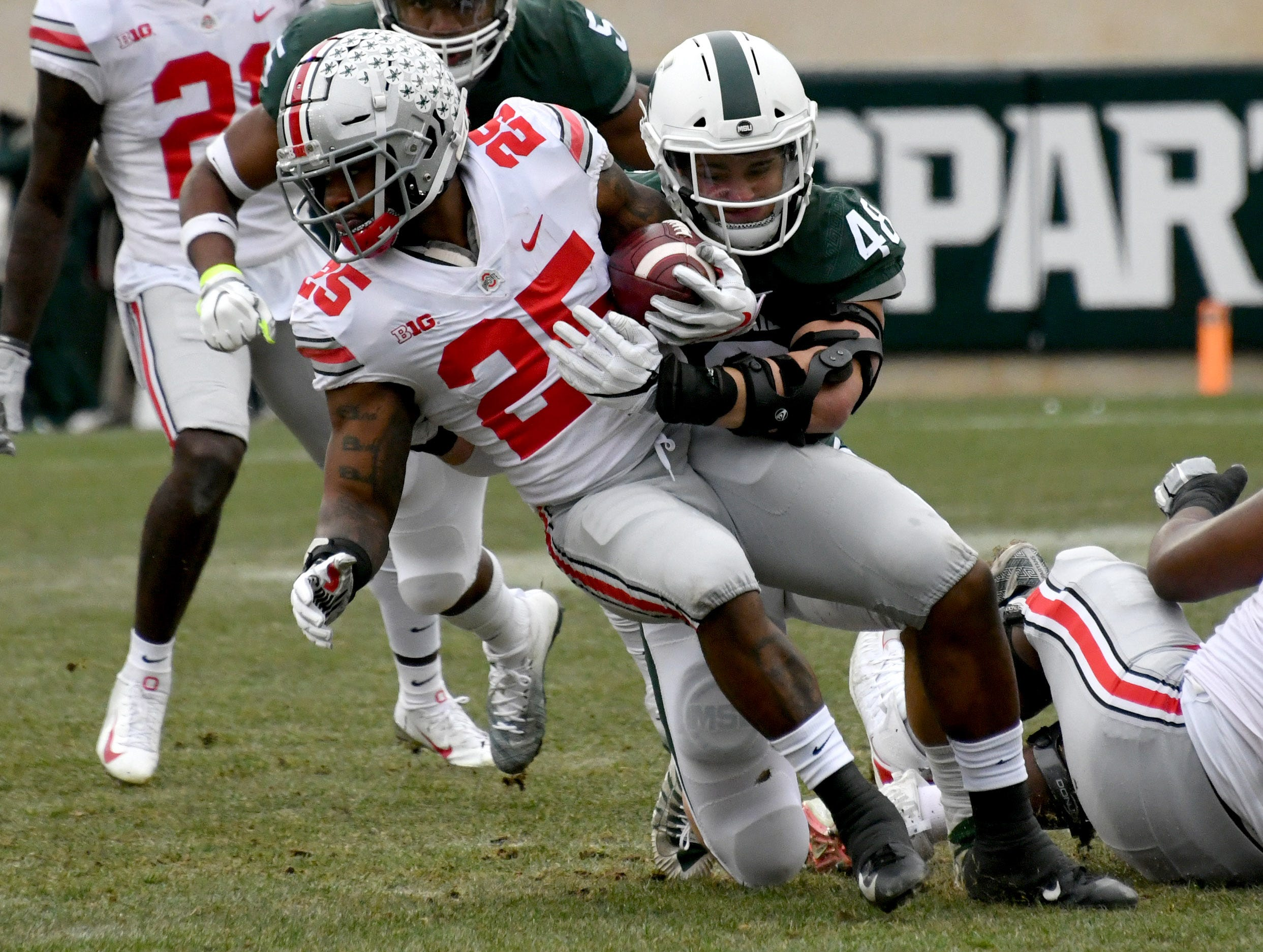 Kenny Willekes tackles running back Mike Weber (25) for a loss in the first quarter.