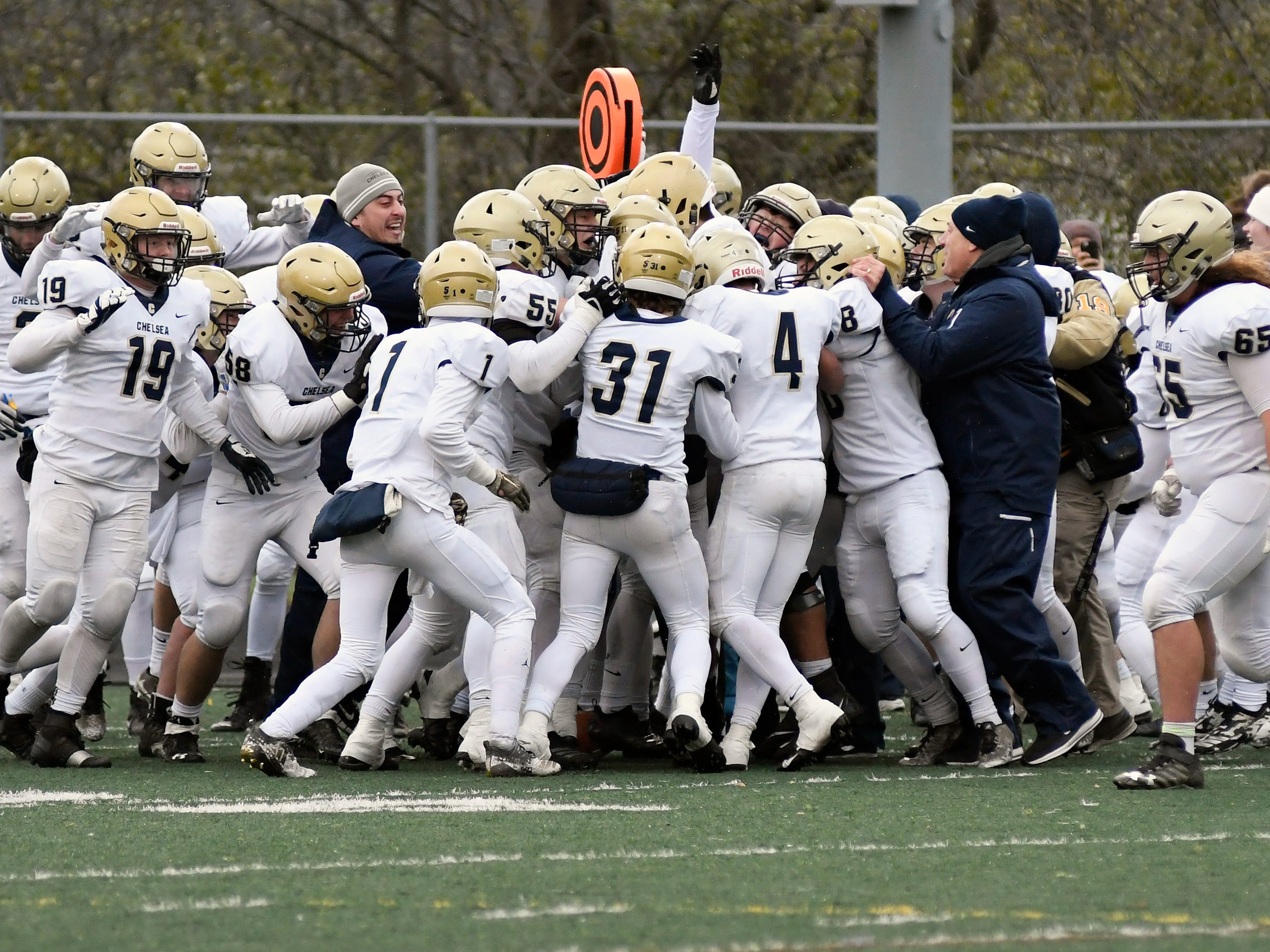 Chelsea free safety Joe Taylor is mobbed by teammates after intercepting a Farmington Hills Harris pass attempt with less than a minute left in the fourth quarter Saturday,  in a Division 4 Regional Final.