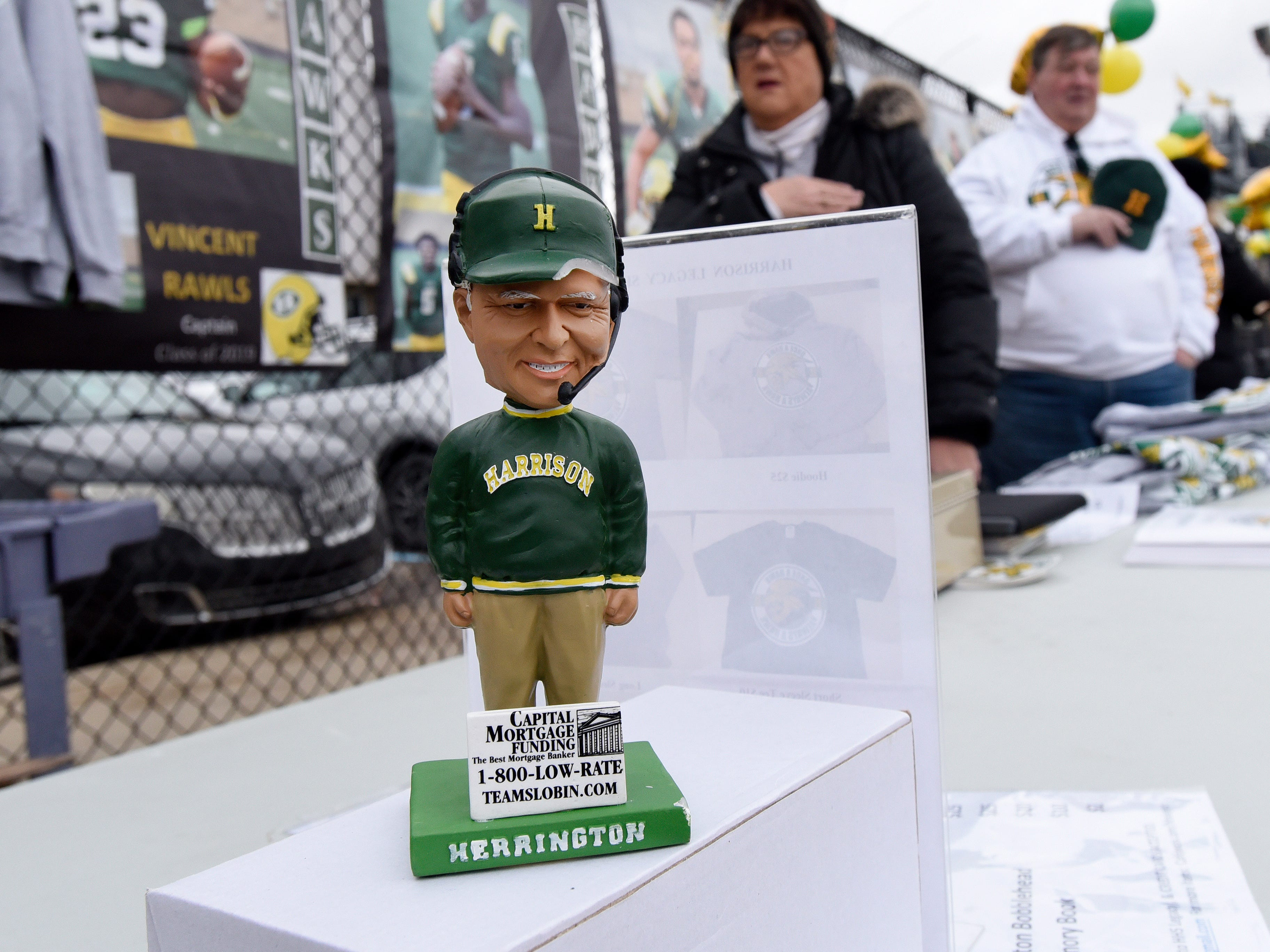 A bobblehead of Farmington Hills Harrison football head coach John Herrington was being sold along the walkway during the game against Chelsea.