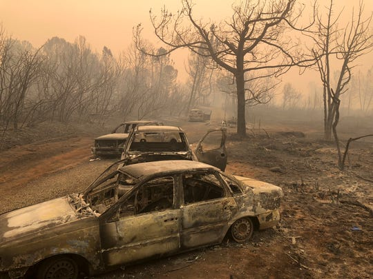 Burned out cars sit on the road side Saturday, Nov. 10, 2018, near Paradise, Calif.