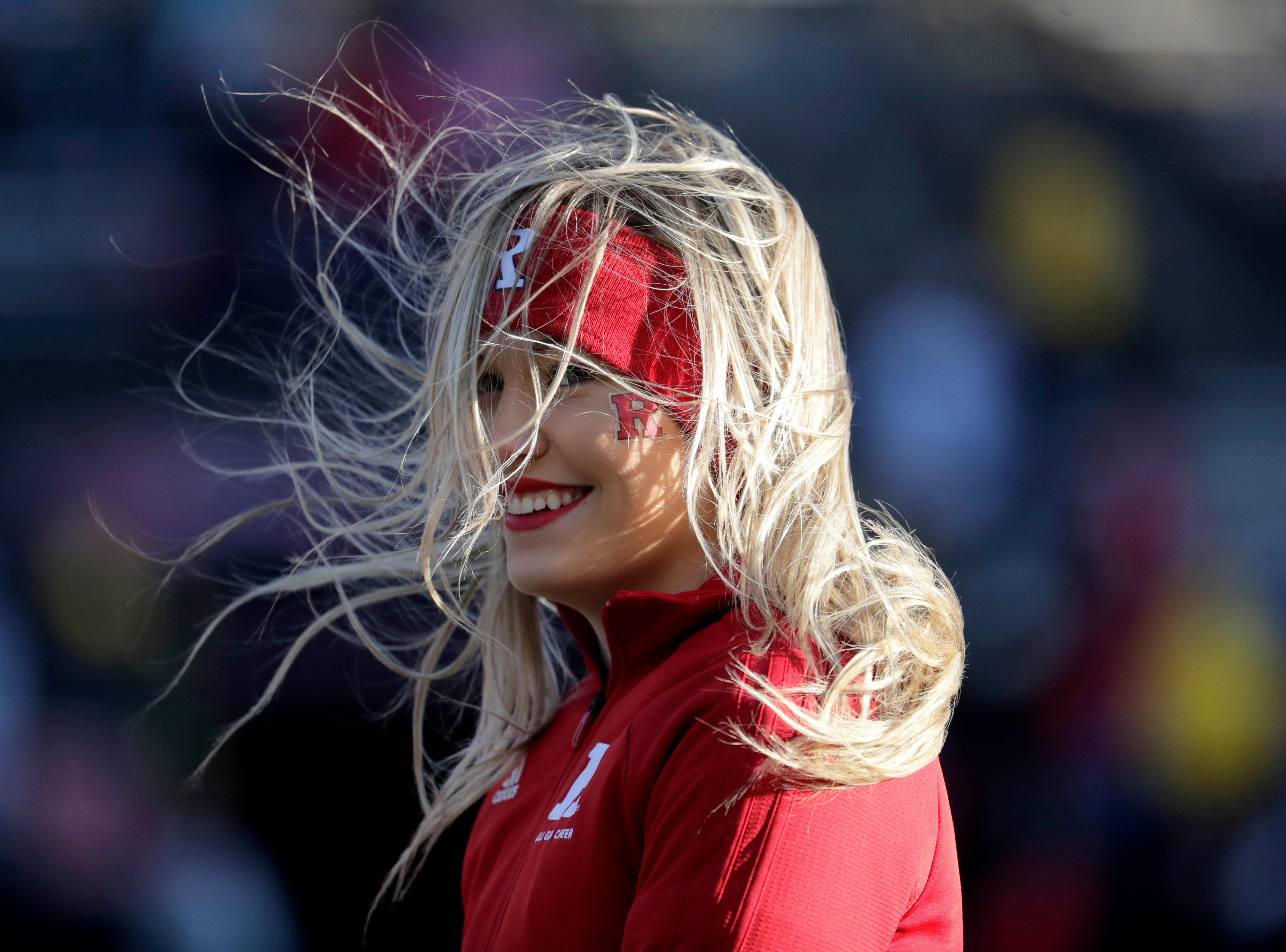 A Rutgers cheerleader stands on the field as gusty winds pick up her hair.