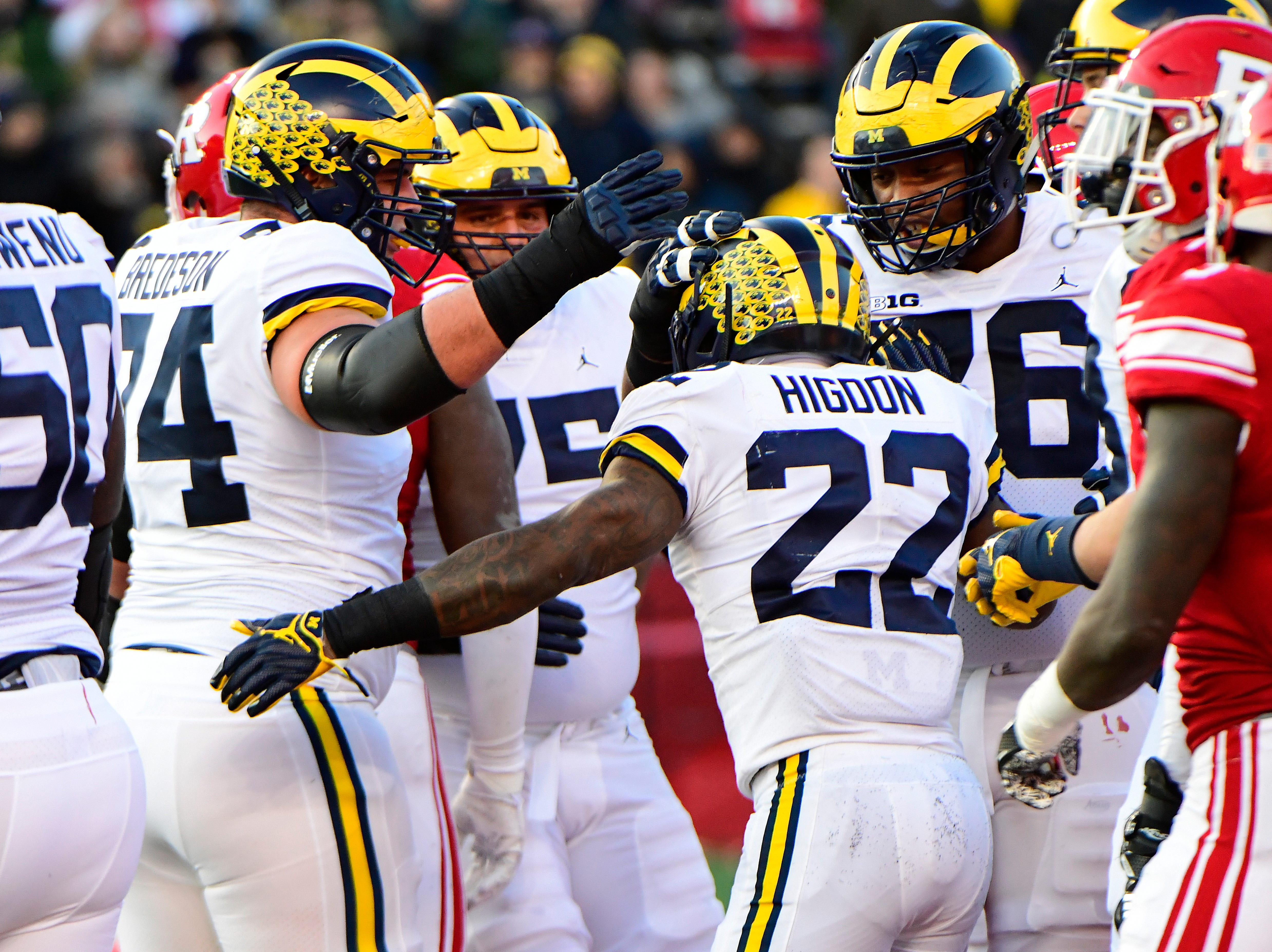 Karan Higdon of the Michigan Wolverines is lauded by teammates after a touchdown against the Rutgers Scarlet Knights during the first quarter.